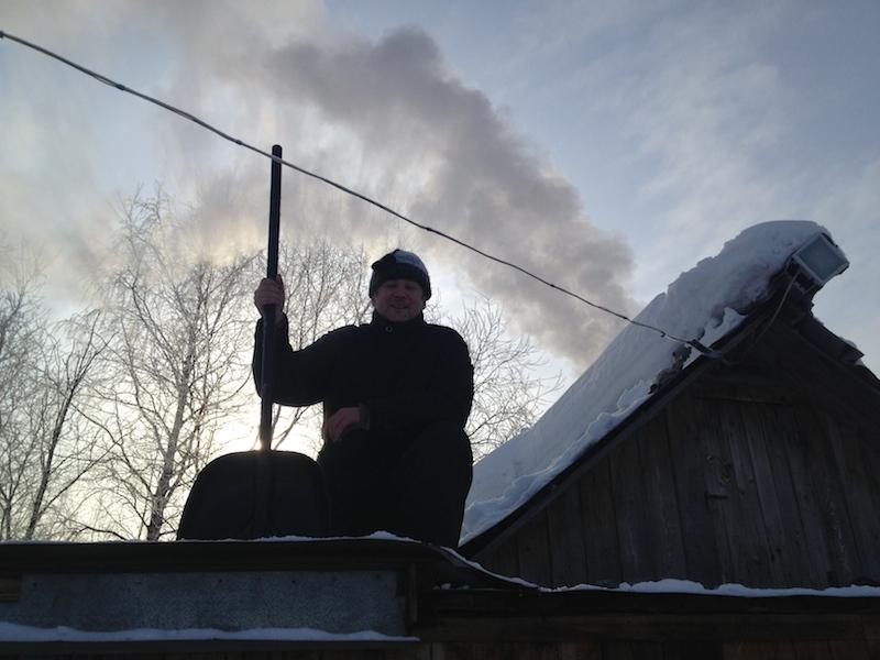 Весенние работы. Мой супруг чистит от снега крышу.